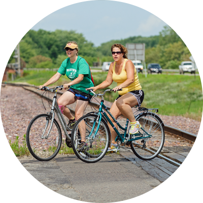Two women biking over a rail crossing